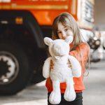 crianca-no-corpo-de-bombeiros-menina-com-um-brinquedo-crianca-perto-do-caminhao-de-bombeiros_1157-46946