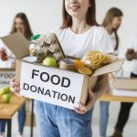 smiley-female-volunteer-holding-donations-box-with-food
